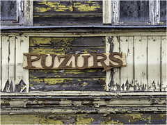 Puzurs. The beautifully sawn-out letters, with the name of a shop, form a great contrast to the neglected maintenance of the facade. (Luc V. de Zeeuw) Tags: facade letters neclected puzurs ventspils latvia