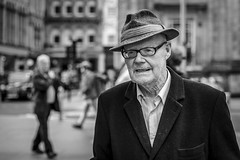 Trilby (Leanne Boulton) Tags: urban street candid portrait portraiture streetphotography candidstreetphotography candidportrait streetportrait eyecontact candideyecontact streetlife old elderly man male face eyes glasses expression emotion mood feeling stubble coat lint hat trilby style fashion tone texture detail depthoffield bokeh naturallight outdoor light shade city scene human life living humanity society culture lifestyle people canon canon5dmkiii 70mm ef2470mmf28liiusm black white blackwhite bw mono blackandwhite monochrome glasgow scotland uk