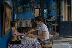 Feeding time (efeardic) Tags: sony alpha 6000 street photography kid girl baby man feeding backgammon blue painting