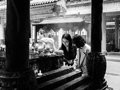 The prayers (Go-tea 郭天) Tags: chongqing républiquepopulairedechine temple old ancient traditional tradition history historical historic construction building religion religious buddha buddhism buddhist incense burn burning pray praying prayer young women lady friend 2 together glasses street urban city outside outdoor people candid bw bnw black white blackwhite blackandwhite monochrome naturallight natural light asia asian china chinese canon eos 100d 24mm prime portrait smoke smog