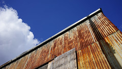 Sky and rust. (Eric Flexyourhead) Tags: vancouver canada britishcolumbia bc olympicvillage city urban detail fragment building old weathered worn patina rust rusty rusting corrugatedmetal sky clear blue bluesky blueskies cloud puffy 169 sonyalphaa7 zeisssonnartfe35mmf28za zeiss 35mmf28