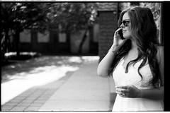 JamieClarkWeddingFilm118 (Johnny Martyr) Tags: leicam6ttl85 leicam6ttl leicam6 leitzsummitar5cmf2 leicasummitar leitzsummitar 50mm 35mm bw blackandwhitefilm women girl woman cell phone rangefinder leica leitz bokeh dress white sunglasses lines portrait profile talking grain trix kodak hc110