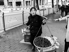 You! (Go-tea 郭天) Tags: chongqing républiquepopulairedechine lady woman seller fruits basket balance heavy hanging hanged pole shoulder hard business walk walking duty busy pointing pointed finger portrait sidewalk boxes street urban city outside outdoor people candid bw bnw black white blackwhite blackandwhite monochrome naturallight natural light asia asian china chinese canon eos 100d 24mm prime plastic bags hand harm