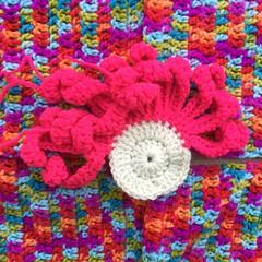 A large crochet flower with grenadine petals on a fiesta background (crochetbug13) Tags: crochet crocheted crocheting crochetflower crochetyarnbomb dayofthedead crochetskull