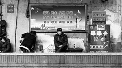 Pending (Go-tea 郭天) Tags: chongqing républiquepopulairedechine man women wait waiting boxes bottles bench advertising avertisement propaganda party communist communism seat seated uniform hat cap officer wall old electric electricity eletrical lines street urban city outside outdoor people candid bw bnw black white blackwhite blackandwhite monochrome naturallight natural light asia asian china chinese canon eos 100d 24mm prime portrait