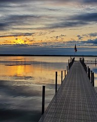 Gull Lake Morning (Mamluke) Tags: gulllake morning am sunrise sunlight clouds sky lake lac water dock flag drapeau dockside minnesota upnorth nuages nubes nubi wolken ciel himmel hemel cielo sun sunlit luzdelsol lucesolare tageslicht zonlicht lumièredusoleil wasser leau aqua acqua lago see meer