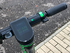 "Closeup of a Lime electric scooter with battery indicator and ""Scan to ride"" on the display"