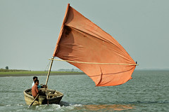 Small boat with as orange sail on the Kaladan River in Sittwe - Myanmar (PascalBo) Tags: nikon d70 burma birmanie myanmar asia asie southeastasia asiedusudest sittwe akyab rakhinestate people boat bateau river rivière man homme outdoor outdoors pascalboegli