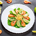 Top view salad with shrimp and slices of line on a black background