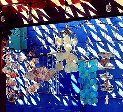 Chimes (Demmer S) Tags: light blue decorative shells seashells lights bulbs hooks hangers cord string cords lines chimes windchimes sun shadows sunshine coastal beach gulfcoast merchandise shopping crafts decor decorate handcrafted art beautiful pretty beachy windchime mobile suncatcher musical sound music sounds chime summer summertime outdoors outside seasonal seasons shadow sunny shop display vendor selling goods retail visual openair retailer seller artsy street streetphotography shootthestreet streetshots documentary urban city urbanphotography streetscene urbanexploration