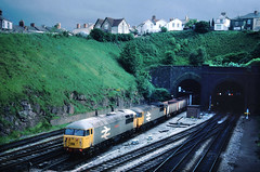 There was a short period when the Grids were tried on these heavy workings.....soon a single class 60 would take over.....56037 Richard Trevethick/045 Cardiff Docks-Llanwern iron ore exiting Hillfield Tunnel Newport 04-06-1987 (the.chair) Tags: 56037 045 cardiff docks llanwern ore hillmend tunnel june 1987