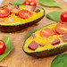 Baked Avocado with Eggs Cherry Tomato and Sausages on the wooden board