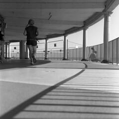Jog On (4foot2) Tags: jogger runner run eastbourne streetphoto streetshot street streetphotography shadows shadow candid candidportrate reportage reportagephotography people peoplewatching interestingpeople colonnade analogue film filmphotography 120film mediumformat bw blackandwhite monochrome mono ilford ilfordhp5plus hp5plus hc110 kodakhc110 kodak rolleiflex rolleiflex35c rollei 2019 fourfoottwo 4foot2 4foot2flickr 4foot2photostream twinlensreflex tlr