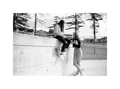 girls in conversation, Dee Why beach, Sydney, winter 2019  #421 (lynnb's snaps) Tags: cvultron35mmf2asphericalv hp5 id11 leicacl bw film rangefinder cvultron35mmf2asphericalvintagemmount 2019 beach deewhybeach sydney australia winter ilfordhp5 leicafilmphotography rangefinderphotography rff filmfilmforever filmneverdie blackandwhite bianconegro biancoenero blackwhite bianconero blancoynegro noiretblanc schwarzweis monochrome ishootfilm girls conversation gossip relaxing street people talking wall casual