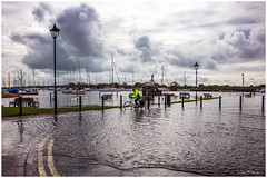 Undeterred (clive_metcalfe) Tags: christchurch dorset england uk flood cyclist stormy weather quay water lamppost boats