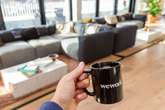 Hand holding a black WeWork cup in front of the joint lounge area of the private office spaces for rent in Cologne, Germany (verchmarco) Tags: köln office cologne thewecompany aktienkurs company startups startup büro labs stock ipo locations softbank wework coworking indoors drinnen coffee kaffee furniture möbel seat sitz contemporary zeitgemäs room zimmer family familie wood holz coffeetable kaffetisch sofa relaxation entspannung table tabelle window fenster interiordesign innenarchitektur chair stuhl noperson keineperson tea tee cozy gemütlich woman frau luxury luxus 2019 2020 2021 2022 2023 2024 2025