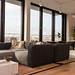 Modern eingerichtete Lounge mit Sofawecke und großer Fensterfront der gemeinschaftlichen Arbeitsraumfläche von WeWork in Köln
