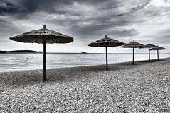 Beach after the seasson (radimersky) Tags: beach plaża sea adriatic morze primošten day monochrome czarnobiałe bw emptiness kamienie stons stony kamienista chorwacja harvatska microfourthirds 43 fourthirds dmclx100 panasonic lumix parasol parasole lx100 moddy nastrojowe sunshade cloudy pochmurno dzien water woda wrocław