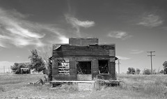 Willard General Store (explore) (unknown quantity) Tags: abandonedbusiness sky clouds openwindows peelingsiding rust opendoorway barewood utilitypoles grass trees monochrome blackandwhite weathered cloudsstormssunsetssunrises