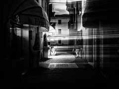 Gardasee Lazise (Sandy...J) Tags: italy city atmosphere alone noir night darkness light monochrom man mood olympus fotografie photography blackwhite bw italien urban street streetphotography sw schwarzweis strasenfotografie stadt stimmung oldtown reflection