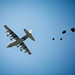 A C-130 aircraft precisely drops cargo during a training exercise