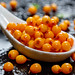 Sea buckthorn berries with water drops in white ceramic spoon on black background
