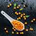 Ripe fruits of sea buckthorn with drops of water on a black background. View from above