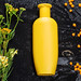 Yellow plastic bottle and sea buckthorn berries and wildflowers on black background. Natural care products
