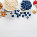 Healthy food background with fresh berries, almonds and oatmeal
