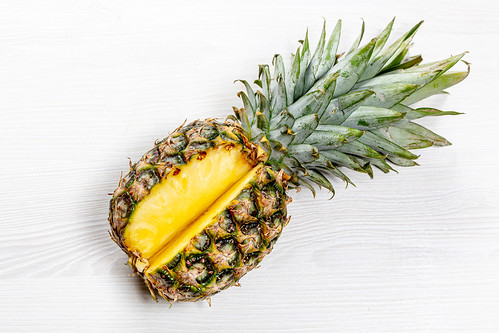 Fresh pineapple with leaves on white wooden background