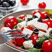 Fork and salad with Basil, tomatoes, black olives and feta cheese