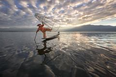 Burmese Fisherman on the Boat with Traditional Conical Net in the Morning, Lake Inle, Myanmar (ansharphoto) Tags: asia asian attraction balance balancing bamboo boat burma burmese canoe catching clouds countryside culture dawn famous fish fisherman fishing inlay inle kayak lake landscape lifestyle local man morning myanmar nature net oar orange oriental outdoor province reflection river rural shan skill state sunrise tourism tradition traditional tranquil trap travel water