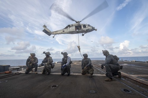 Sailors assigned to Special Boat Team 12 and Explosive Ordnance Disposal (EOD) Mobile Unit 5 fast rope from a MH-60S Sea Hawk helicopter.