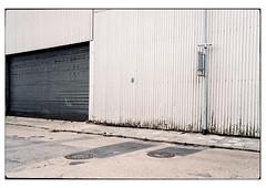 (schlomo jawotnik) Tags: 2019 juli emden ostfriesland strase gebäude rolltor blech strasenschild gullideckel hinweisschild asphalt unkraut analog film kodak kodakproimage100 usw