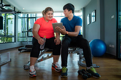 Asian fat girl reading a fitness program from her trainer (I love landscape) Tags: woman effort lifter care indoors healthy slim plan membership control diet program menu discuss result report overweight fat thai asia asian girl sport gym workout people personal weight female man wellness trainer fitness fit clipboard training lifestyle health working exercise active athlete club body happy bodybuilding person dumbbell lifting muscles