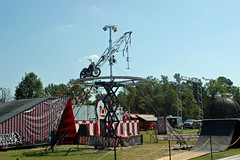 Cycle Circus Ready For The Next Show. (dccradio) Tags: lumberton nc northcarolina robesoncountyfair sky bluesky outdoors outdoor outside robesonregionalagriculturalfair fair countyfair fun entertainment communityevent nikon d40 dslr weekend september sunday sundayafternoon afternoon goodafternoon tree trees greenery foliage branch treebranch branches treebranches prop cyclecircus circusprop motorbike motorcycle dirtbike aerialistprop johnnyrocketscyclecircus grass lawn yard ramp ramps backwall backdrop red white stripes