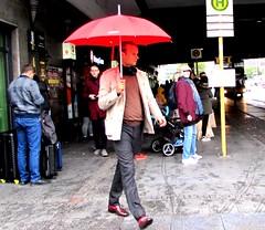 Red umbrella (thomasgorman1) Tags: people sidewalk canon man walking tourist tourists travel corner street streetshots streetphotos pedestrian red raining berlin germany alexanderplatz sign crowd