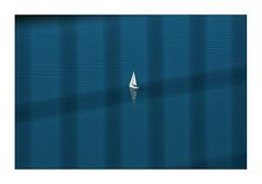 boat on a lake - seen through a fence layer (Armin Fuchs) Tags: arminfuchs nomansland fence diagonal layer naturallayer boat lake water blue white reflection anonymousvisitor thomaslistl wolfiwolf jazzinbaggies hff