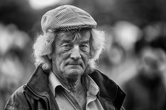 Looking my way (Frank Fullard) Tags: frankfullard fullard candid street portrait face expression hair cap irish ireland galway black white blanc noir serious monochrome glare looking