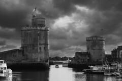 Les tours de La Rochelle (N.Hell) Tags: tower turret mood dark cloud sky atmosphere monochrome bw blackwhite landscape cityscape scary old grey canon 50d sigma 70200mm water ocean sea seaside harbour boat ship atlantic city town larochelle urban view scenery