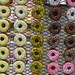Multicolored view of many donuts displayed in rows with different types of icing
