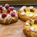 Danish pastries with raspberries and sugar icing on a wooden board
