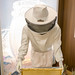 Symbolic picture of honey preparation and apiculture: beekeeper in protective suit at the beehive to harvest honey