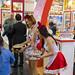 Hostessen in rot-schwarzem Kleid bieten Kindern Süßigkeiten an bei der Anuga Lebensmittelmesse in Köln