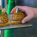 Rangeland foods - Hand greift ein Burgerstück von einem Probiertablet