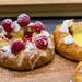 Puddingplunder mit Himbeeren und Zuckerguss auf einem Holzbrett