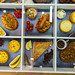 Top view of variety of pastries: fruit tartlets, brown coffee cookies, cinnamon apple turnover  and sausage-pizza