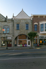Building — Mount Sterling, Kentucky (Pythaglio) Tags: building structure historic commercial twostory stone rusticated romanesque roundarched storefront 11windows pedimented finials sidewalk street kentucky montgomerycounty mountsterling 1891