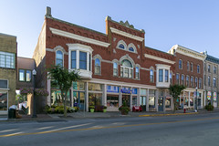 Building — Mount Sterling, Kentucky (Pythaglio) Tags: building structure historic twostory brick romanesque corbelling corbelled orielwindows storefronts stonework roundarched 11windows voussoirs stringcourse sidewalk street kentucky montgomerycounty mountsterling