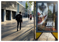 Walkers to the Left of Me, Joker to the Right (Dave Button) Tags: joker suit businessman walk fuji fujifilm colour color provia xe2 xe2s walking barcelona barceloneta shadows busstop movieposter street urban streetphotography spain catalunya